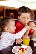 Little girl sharing her dessert with her brother Stock Photos