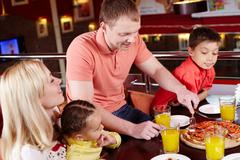 Family gathered together to enjoy pizza at the local pizzeria Stock Photos