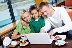 parents and their male kid using the cafe wi-fi to surf the internet - stock photo