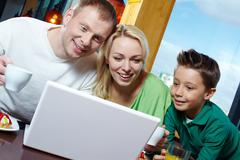 Family of three being amazed with the stuff displayed on the laptop screen Stock Photos