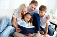 Stock Photo of portrait of happy family with two children reading book