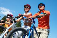 Stock Photo of portrait of happy family on bicycles against blue sky
