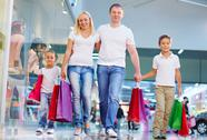 Portrait of modern family with paperbags walking in the mall Stock Photos