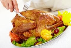 Image of roasted turkey being cut by a human Stock Photos