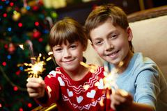 portrait of happy siblings with bengal lights on christmas evening - stock photo