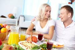 Portrait of happy couple sitting at festive table and looking at one another Stock Photos