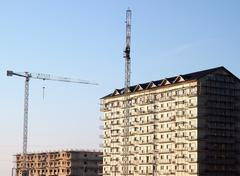 Stock Photo of cranes next to buildings covered in scaffolds