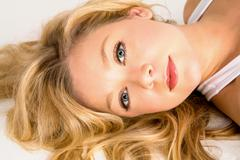 Beautiful blonde woman laying down Stock Photos