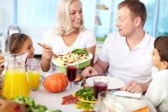 Portrait of happy couple and their kids sitting at festive table and going to ea Stock Photos