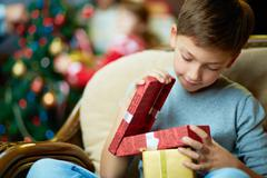 Portrait of adorable boy with giftboxes looking into one of them Stock Photos