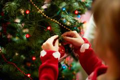 Close-up of child hanging decorative toy ball on christmas tree branch Stock Photos