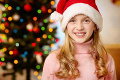 Adorable girl in santa hat looking at camera with smile Stock Photos