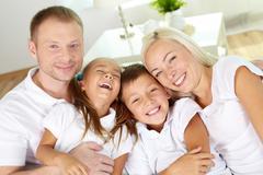 Muotokuva onnellinen vanhempien ja nauraa lasten katsot kameraan Kuvituskuvat