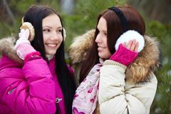portrait of two pretty girls in winter park looking at each other with smiles - stock photo