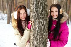 portrait of two pretty girls standing by tree trunk in winter park and looking a - stock photo