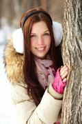 portrait of pretty girl standing by tree trunk in winter park and looking at cam - stock photo