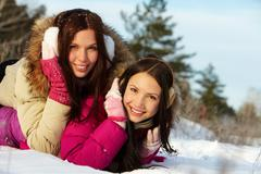 portrait of two pretty girls lying on snow and looking at camera - stock photo
