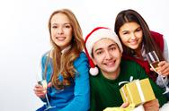 Image of teenage friends with champagne and gifts looking at camera Stock Photos