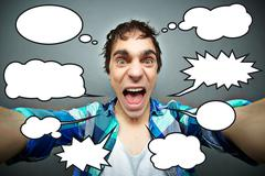 young man shouting angrily or crazily at camera, numerous speech bubbles - stock photo