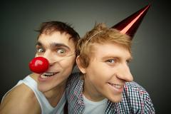 two funny guys making faces at camera celebrating fool's day - stock photo