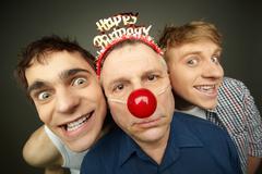 two guys having fun playing pranks on a senior man celebrating birthday or fool' - stock photo
