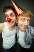 kaksi hauska kaverit katsot kameraa ja hymyilee Järjettömän, tyhmä päivä sarja - stock photo