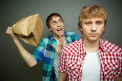 crazy guy being ready to explode paper bag behind his friend back - stock photo