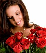 Young brunette admiring her roses Stock Photos