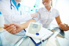 Close-up of tonometer by patient's arm during blood pressure measuring at medica Stock Photos