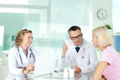 Doctor describing vitamins to patient at medical consultation Stock Photos