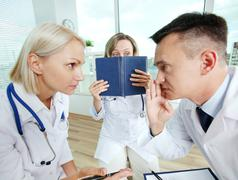 Portrait of male clinician and his colleague conspiring with scared co-worker ne Stock Photos
