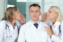 Portrait of pensive male clinician between two gossiping women Stock Photos