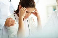 Portrait of woman with headache touching her temples with medical staff supporti Stock Photos