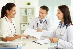 Medical assistant giving the prescription to the smiling patient Stock Photos
