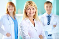 Portrait of pretty clinician in white coat looking at camera with smile Stock Photos