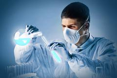 young masked chemist ready to pour one chemical into another - stock photo