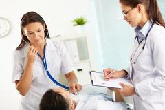 Doctor listening to the patient's internals using stethoscope, nurse taking note Stock Photos