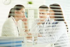 Unhappy female patient sitting in the doctor's office, practitioners taking care Stock Photos
