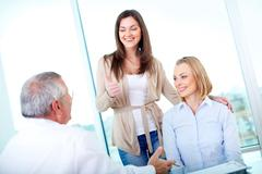 Portrait of female patient showing thimb up with her friend at medical consultat Stock Photos