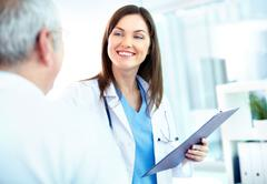portrait of young pretty assistant looking at clinician while interacting with h - stock photo