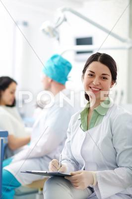 Stock photo of pretty nurse looking at camera with smile on background of dentist and patient