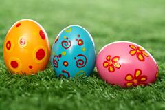 three easter eggs lying on the lawn - stock photo