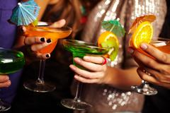 young people holding cocktails, their faces being offscreen - stock photo