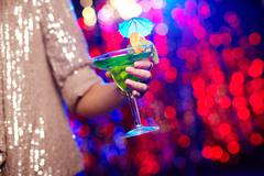 Girl in a glamorous outfit holding a cocktail with tropical fruit Stock Photos