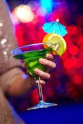 Young woman in a sparkling dress holding a cocktail at a party Stock Photos