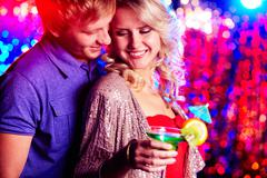 Young couple flirting at party against sparkling background Stock Photos
