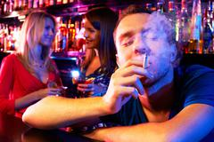 portrait of young man smoking in the bar with two girls on background - stock photo