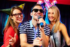 Portrait of happy friends singing in microphone in the karaoke bar Stock Photos
