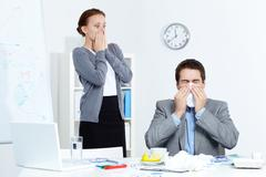 image of businessman sneezing while his partner looking at him with fright in of - stock photo