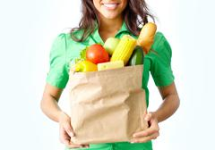 Image of paper packet full of different fruits and vegetables held by female Stock Photos